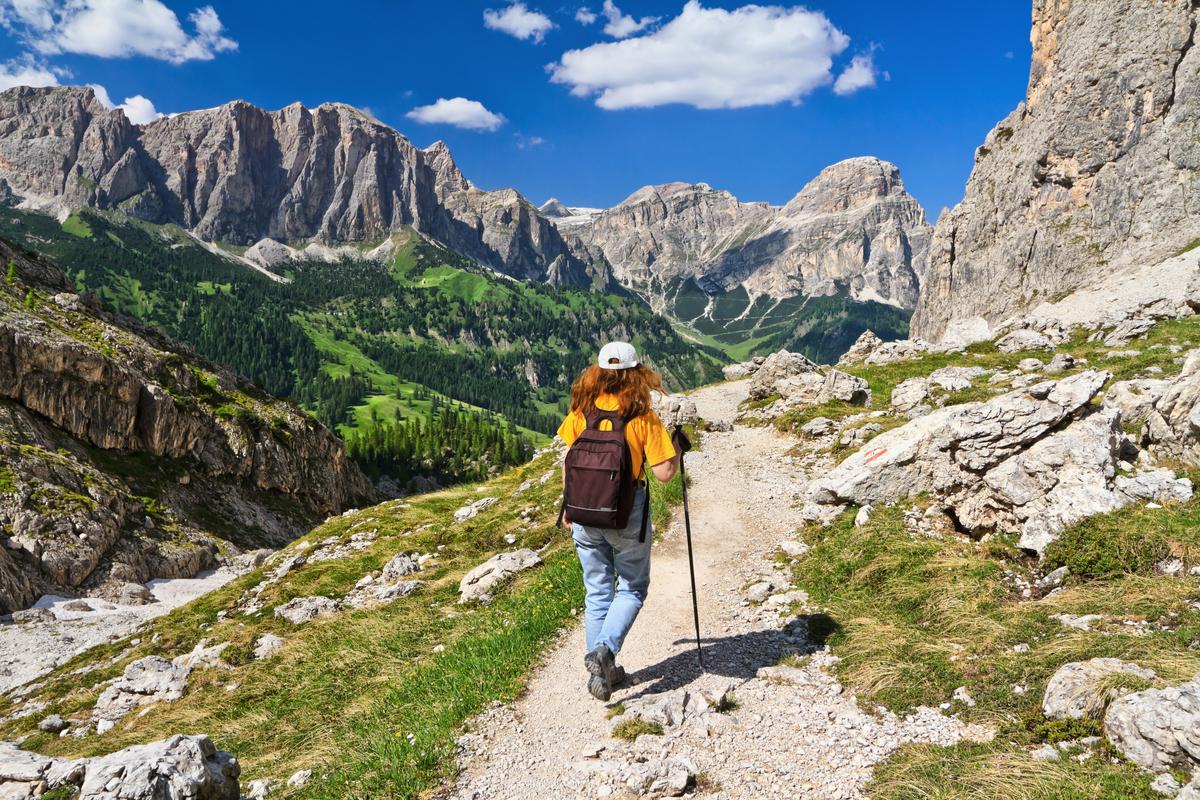 donna percorre sentiero tra le montagne