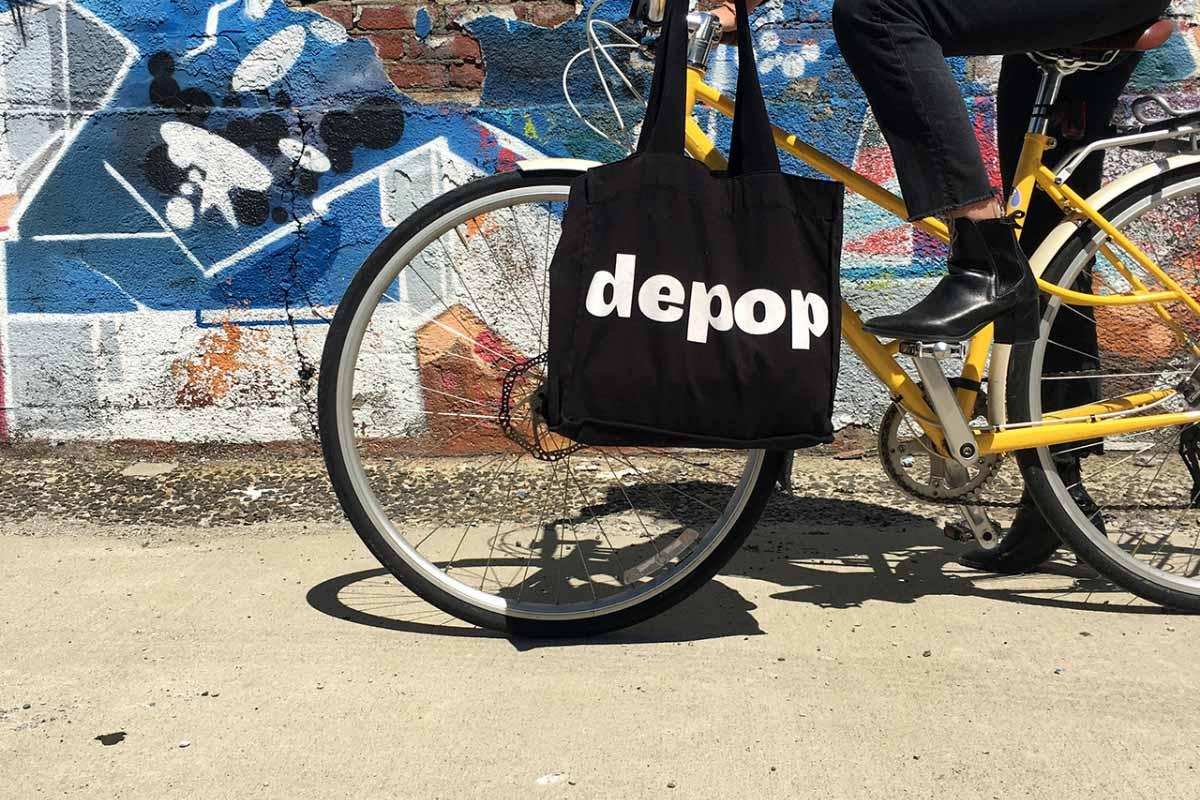 ragazza in bici con shopper nera Depop