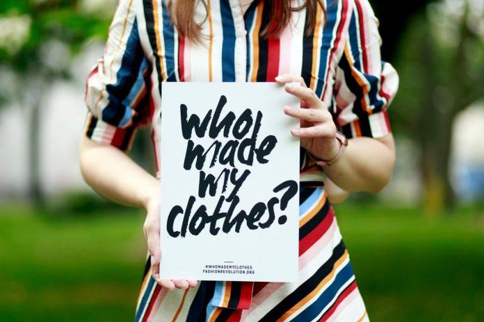 Donna che regge cartello con scritta Who made my clothes?