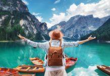 ragazza di spalle davanti ad un lago di montagna fa ecoturismo