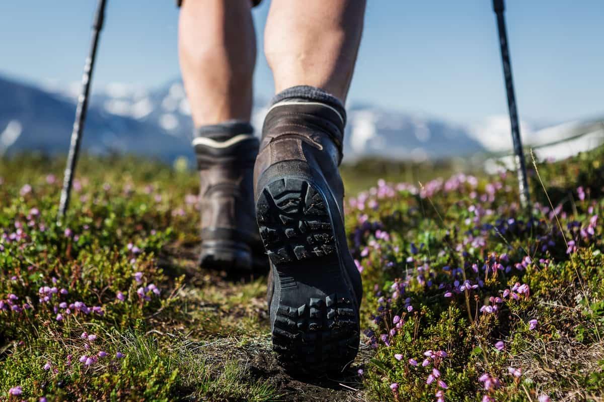 ragazza che cammina con scarponi da hiking su prato fiorito