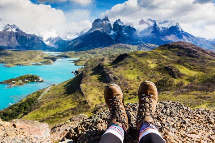 piedi di una ragazza che fa hiking su sfondo con montagna e lago