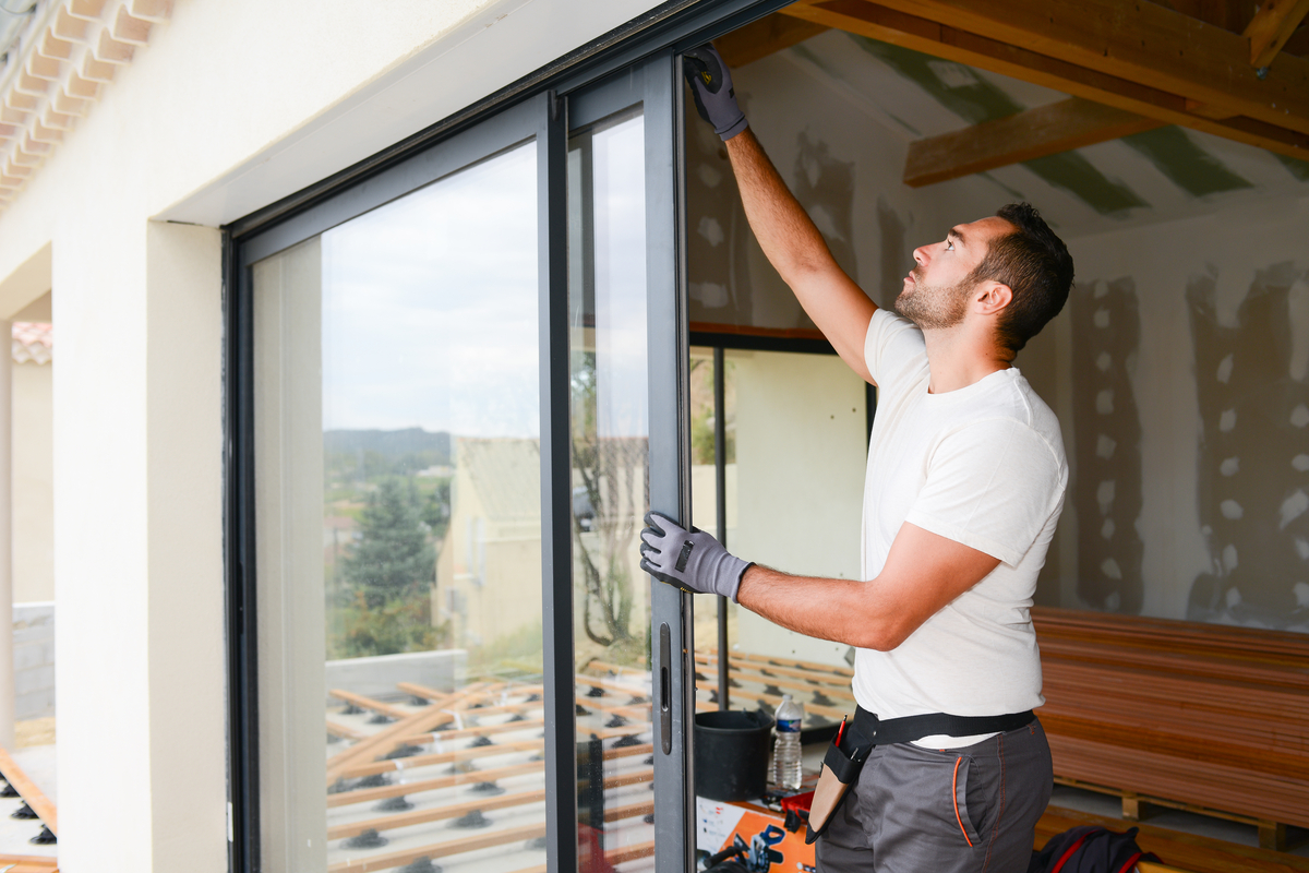 uomo ripara infissi di una finestraa