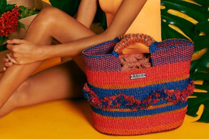 Donna che mostra una borsa in raffia AAKS