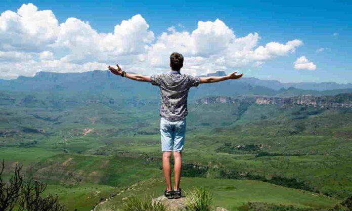 uomo in piedi davanti ad un paesaggio di montagna