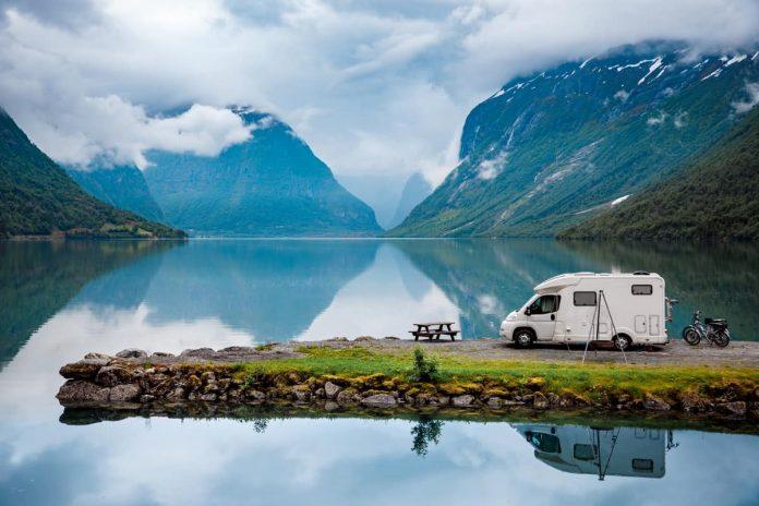 camper parcheggiato sulla riva di un lago tra le montagne