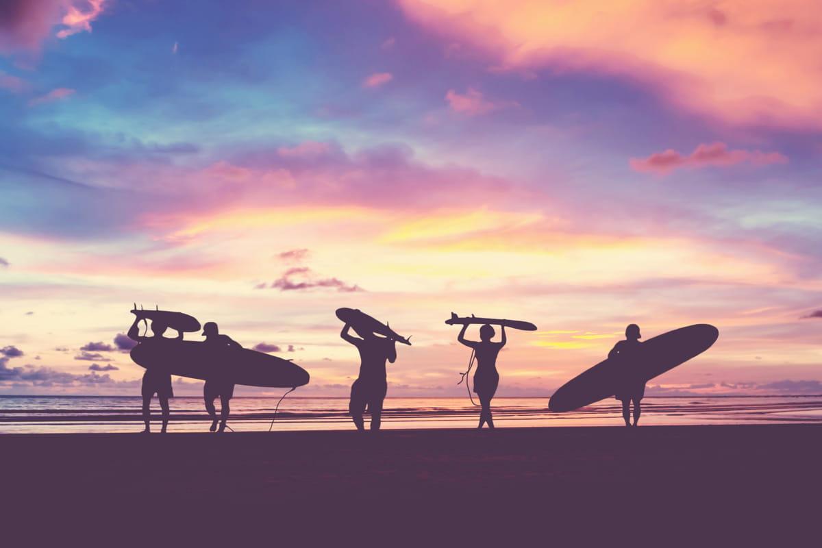 cinque ragazzi con tavole da surf sulla spiaggia