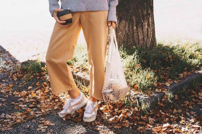 Donna che indossa pantaloni beige in un bosco autunnale