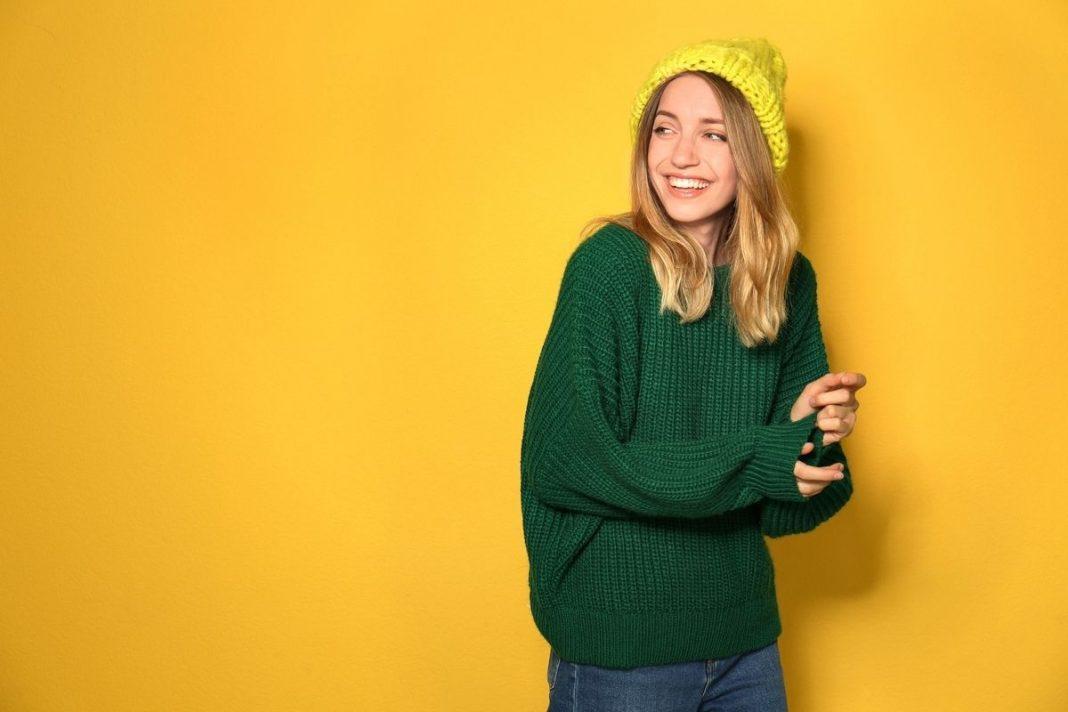 ragazza che indossa un maglione verde su fondo giallo